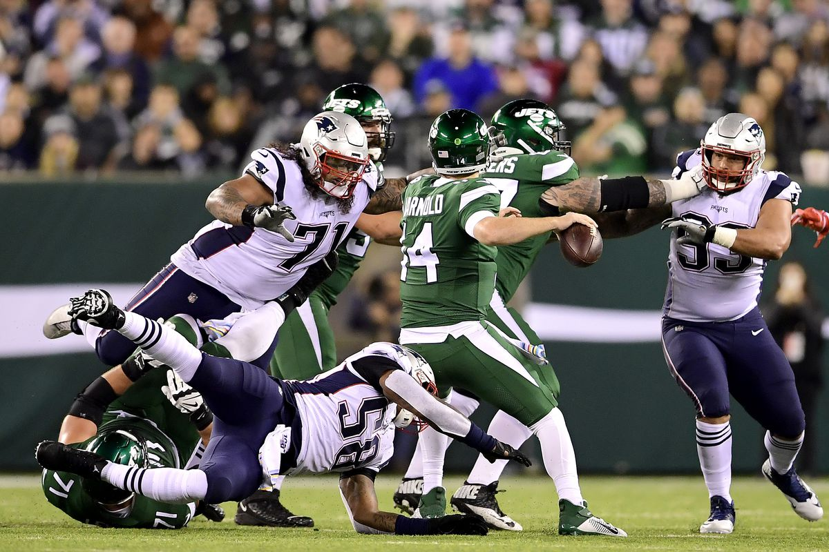 Danny Shelton of the New England Patriots is called for roughing the passer as he hits Sam Darnold of the New York Jets during the first half at MetLife Stadium on October 21, 2019 in East Rutherford, New Jersey.
