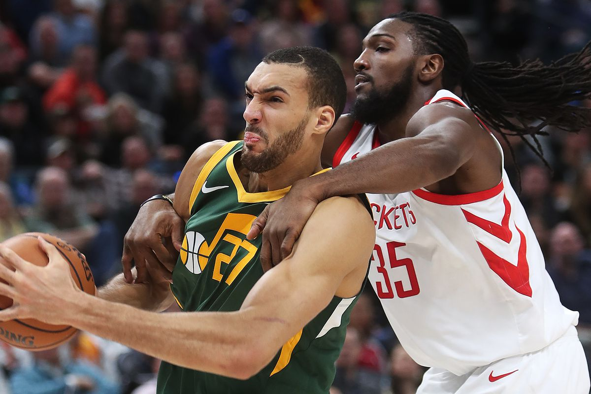 Utah Jazz center Rudy Gobert (27) is fouled by Houston Rockets forward Kenneth Faried (35) under the basket as the Utah Jazz and the Houston Rockets play an NBA basketball game at Vivint Smart Home Arena in Salt Lake City on Saturday, Feb. 2, 2019.