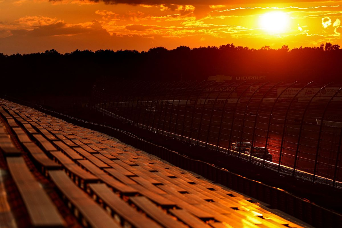 Cars race during sunset in front of empty grandstand spectator seating during the NASCAR Cup Series Pocono 350 at Pocono Raceway on June 28, 2020 in Long Pond, Pennsylvania. The NASCAR series is currently racing without fans due the Covid-19 pandemic.