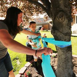 Natalie Hansen and her son Tobin tie a large ribbon on a tree as community members gather to tie ribbons and write messages to the Rackley family and first responders of the murder-suicide along Alta Canyon Drive in Sandy on Saturday, June 10, 2017.