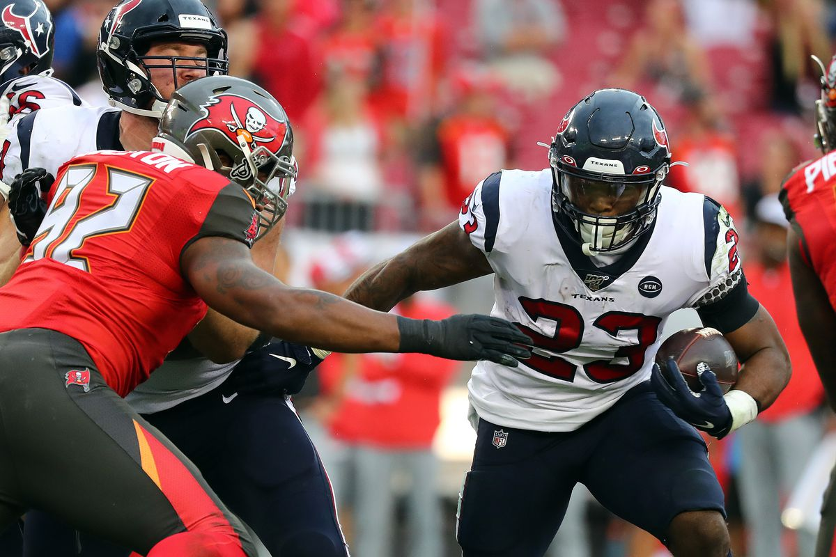 Houston Texans running back Carlos Hyde runs with the ball as Tampa Bay Buccaneers defensive tackle William Gholston defends during the second half at Raymond James Stadium
