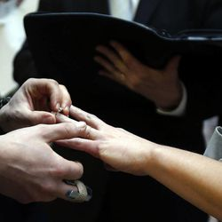 Jax Collins places a ring on the hand of Heather Collins as they are married outside the Salt Lake County clerk's office, Monday, Dec. 23, 2013. U.S. District Judge Robert Shelby denied a motion by the state of Utah to halt same-sex marriages pending an appeal.