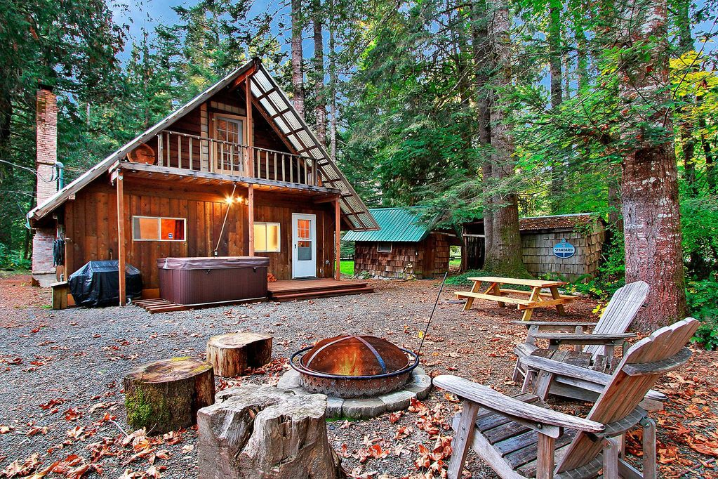 A seating area with stumps, adirondack chairs, and a fire pit sits in front of a wooden A-frame house, hot tub, and picnic table.