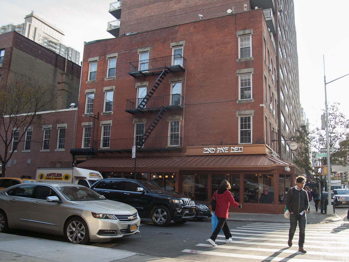 A brick building in New York City with 2nd Ave Deli on the ground floor