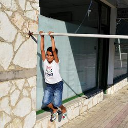 Cidra Al-Hamadan, 8, from Damascus, Syria, swings from a pole holding up an awning outside a poolside bar that has been transformed into a kindergarten at the Kyllini refugee camp near Myrsini, Greece, July 11, 2016. The camp was previously a luxury resort before it fell into disrepair and was later turned into a refugee camp.