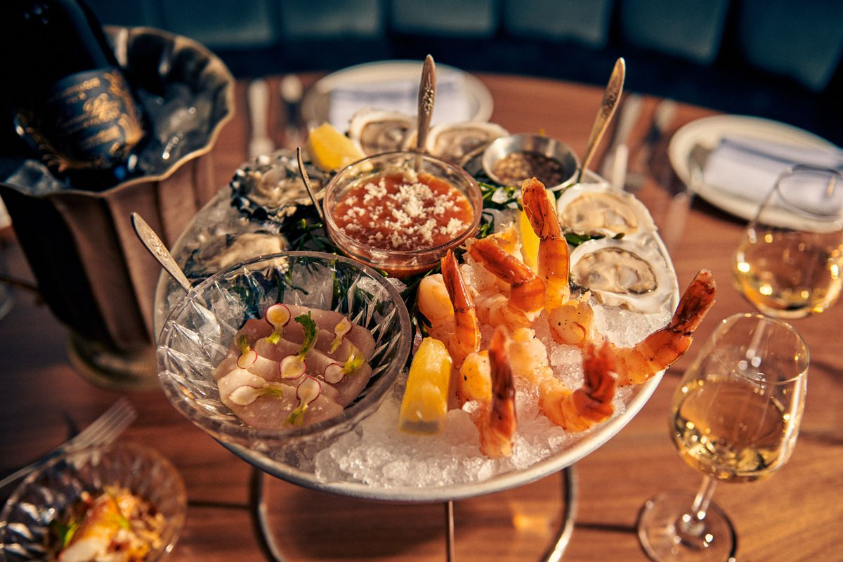 A shellfish platter with shrimp cocktail, hamachi, oysters sits just two glasses of Champagne at the Riddler