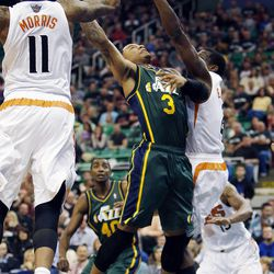 Trey Burke (3) of the Utah Jazz goes up for a shot against Phoenix during NBA basketball in Salt Lake City, Friday, Nov. 29, 2013. At left is Markieff Morris (11) of the Phoenix Suns.