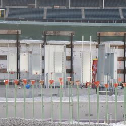 Metal cabinet boxes being installed on the inner right-field wall -
