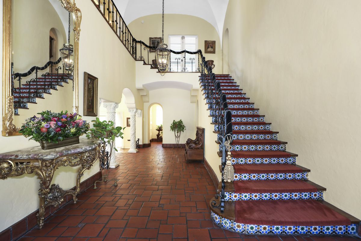A tall entry room with a stairwell on the right and a tiled corridor on the left