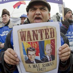 """An anti-government protester holds a poster depicting the country's President Traian Basescu, right, and former communist dictator Nicolae Ceausescu, left, with the legend """"There is one left"""", in Bucharest, Romania, Tuesday, Jan. 24, 2012. Thousands, from all over Romania, joined protests in the Romanian capital asking for the resignation of the country's president and calling for early elections."""