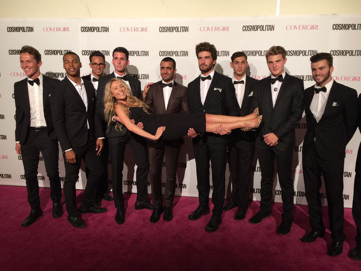 """ManServants perform the """"Photo Booth"""" stunt, posing with attendees for pictures, at Cosmo's 50th Anniversary Party."""