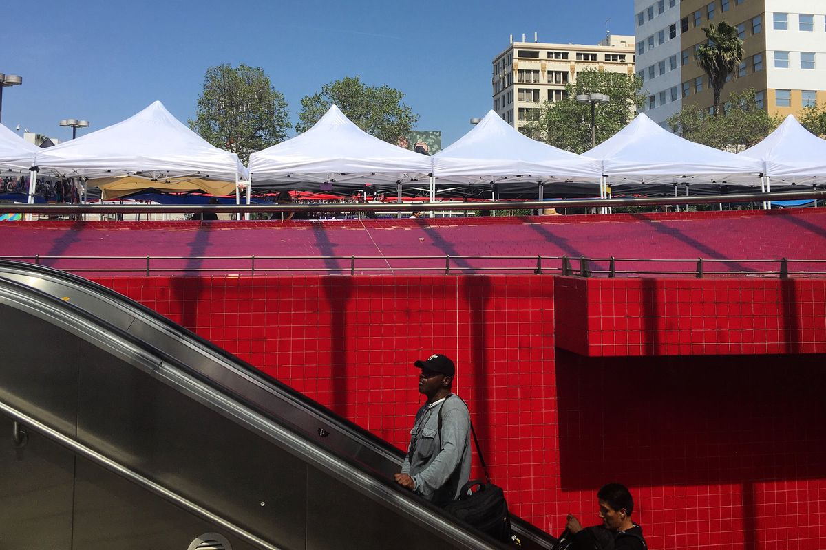 A photo of a man riding an escalator out of the Westlake/MacArthur park subway station, with a wall of red tile in the background.
