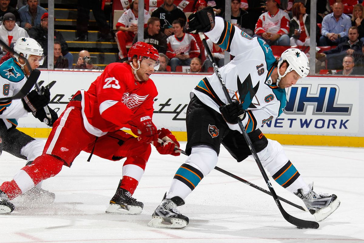 DETROIT, MI - OCTOBER 28:  Joe Thornton #19 of the San Jose Sharks tries to control the puck in front of Brad Stuart #23 of the Detroit Red Wings at Joe Louis Arena on October 28, 2011 in Detroit, Michigan.  (Photo by Gregory Shamus/Getty Images)