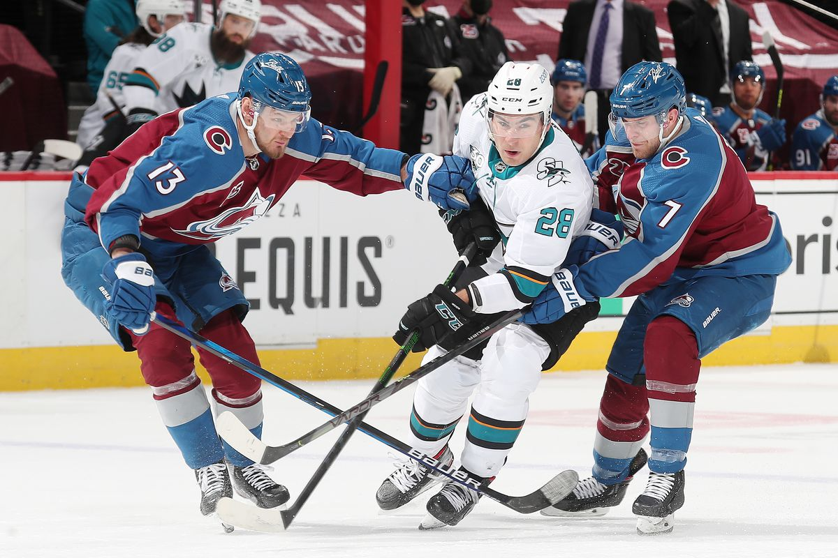Devon Toews #7 and teammate Valeri Nichushkin #13 of the Colorado Avalanche defend against Timo Meier #28 of the San Jose Sharks at Ball Arena on April 30, 2021 in Denver, Colorado.