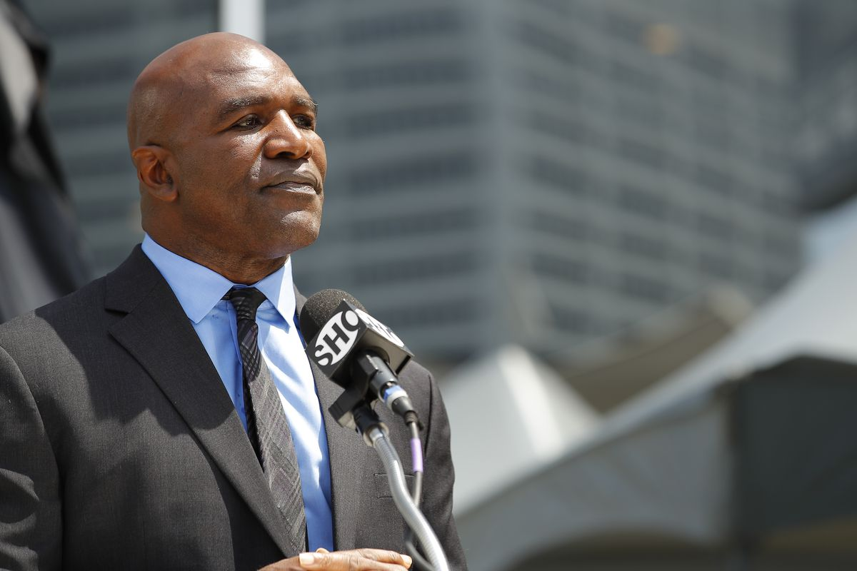 Evander Holyfield speaks at the podium during the unveiling of his statue at State Farm Arena on June 25, 2021 in Atlanta, Georgia.