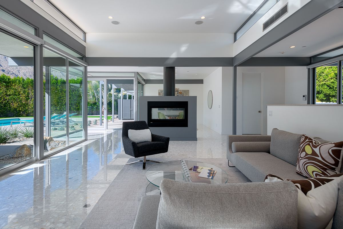 A modern living room with couches, a black chair, a fireplace, and walls of glass.