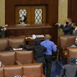 U.S. Capitol police officers point their guns at a door that was vandalized in the House Chamber during a joint session of Congress on January 06, 2021 in Washington, DC. Congress held a joint session today to ratify President-elect Joe Biden's 306-232 Electoral College win over President Donald Trump. A group of Republican senators said they would reject the Electoral College votes of several states unless Congress appointed a commission to audit the election results.