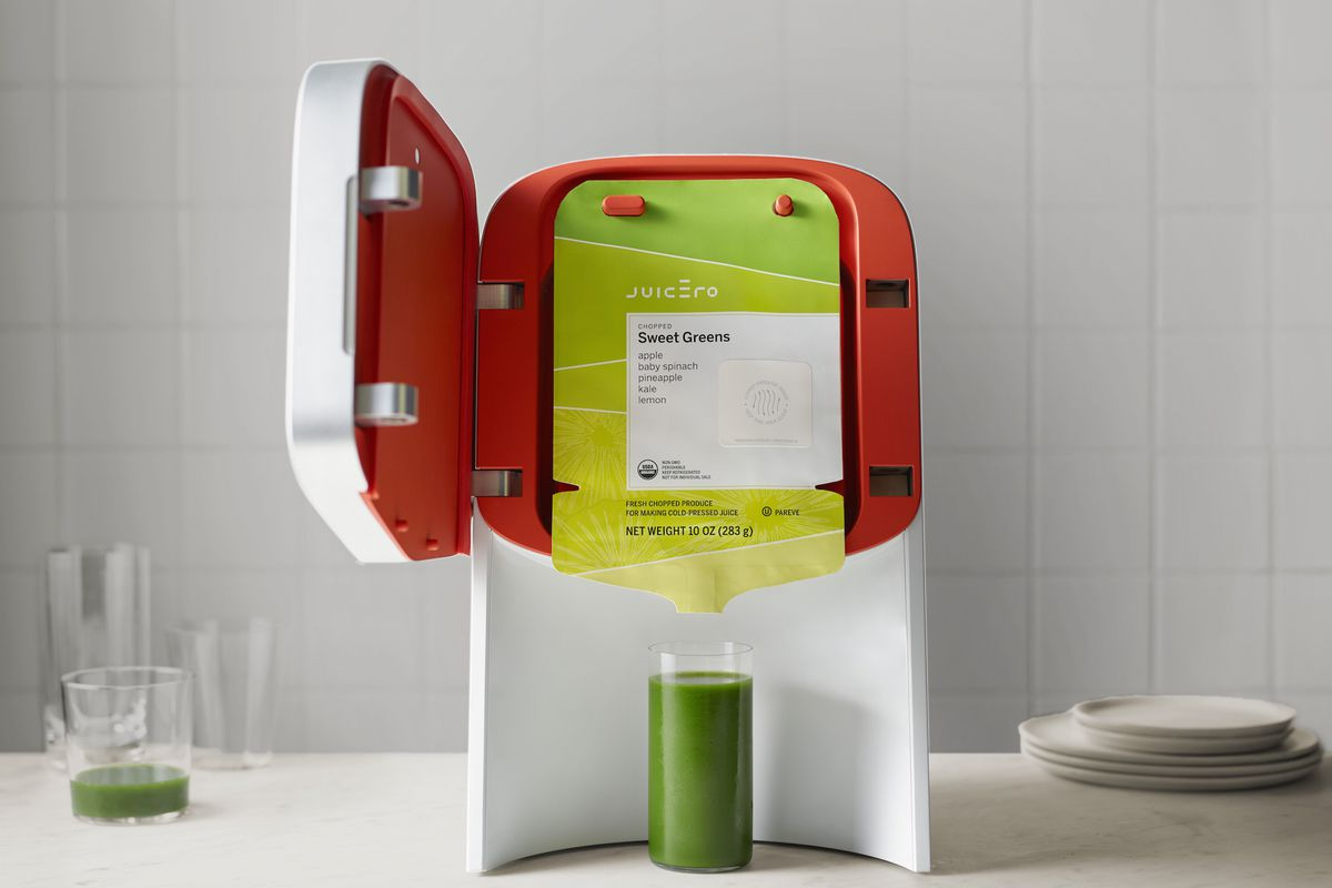 The Juicero juice press after it has pressed a full glass of green juice.