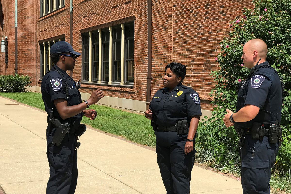 Indianapolis Public Schools Police Department Chief Tonia Guynn talks to two other officers working for the district in front of a school building