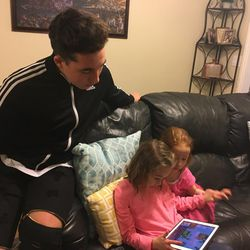 Levi Hilton watches as his sisters playtest his app.