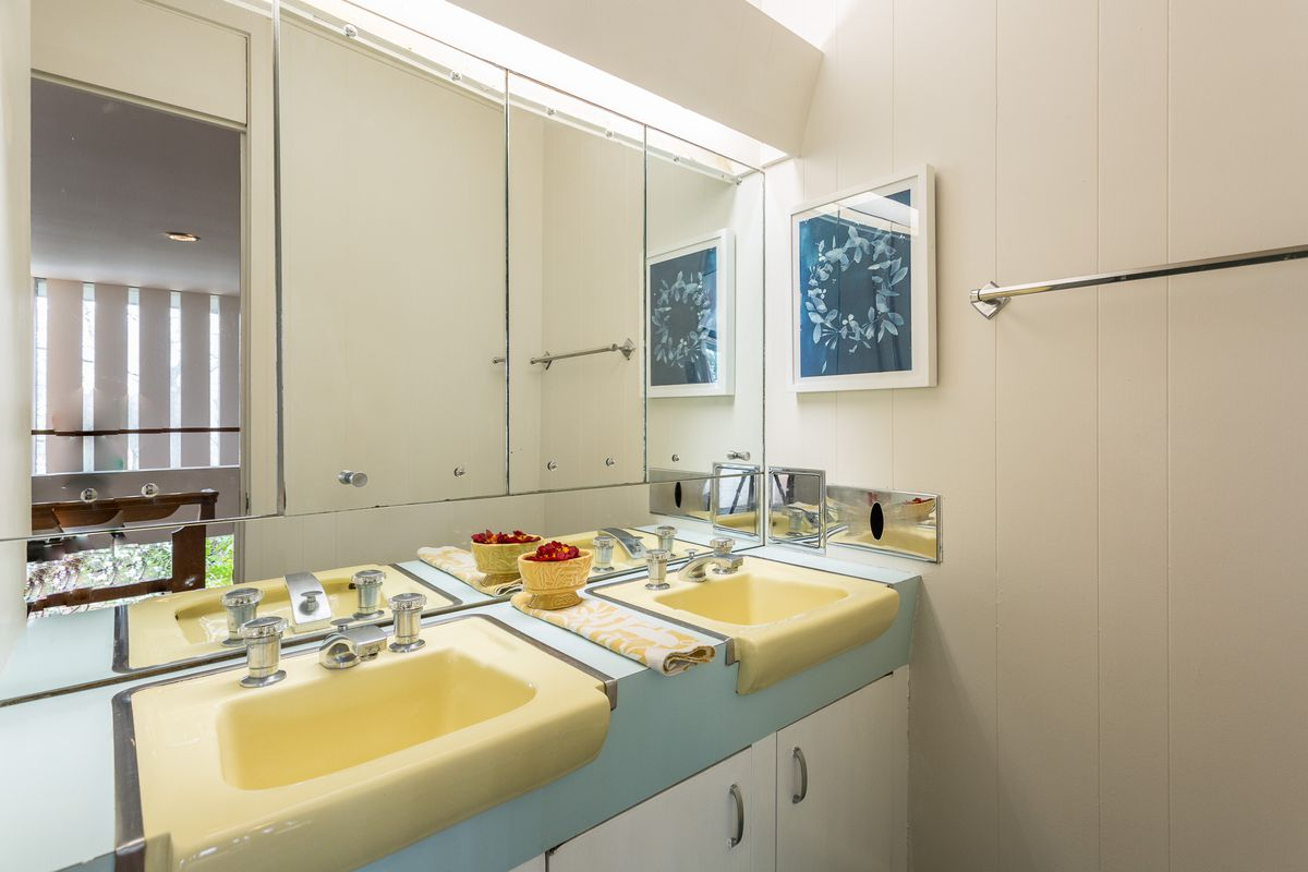 A vintage bathroom with two yellow sinks, blue counters, and a large mirror.