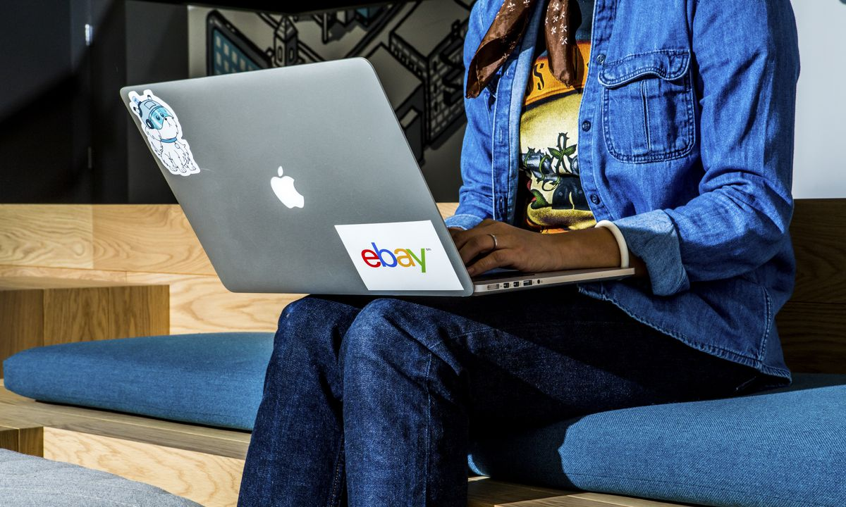 A woman using a laptop with an eBay sticker