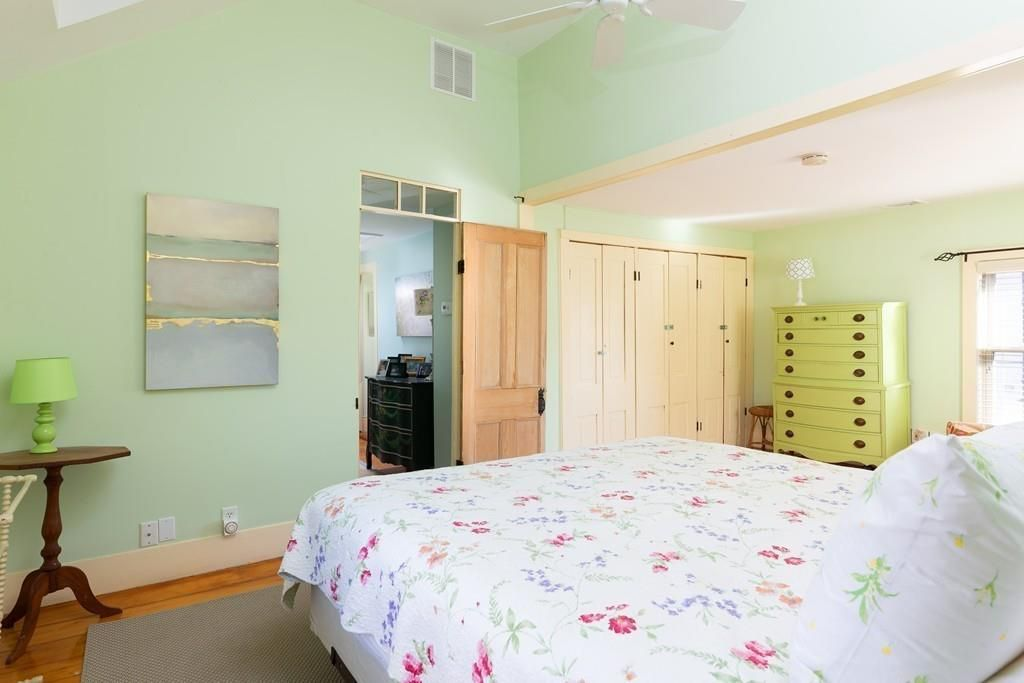 A bedroom with a bed and a large closet with the doors closed.