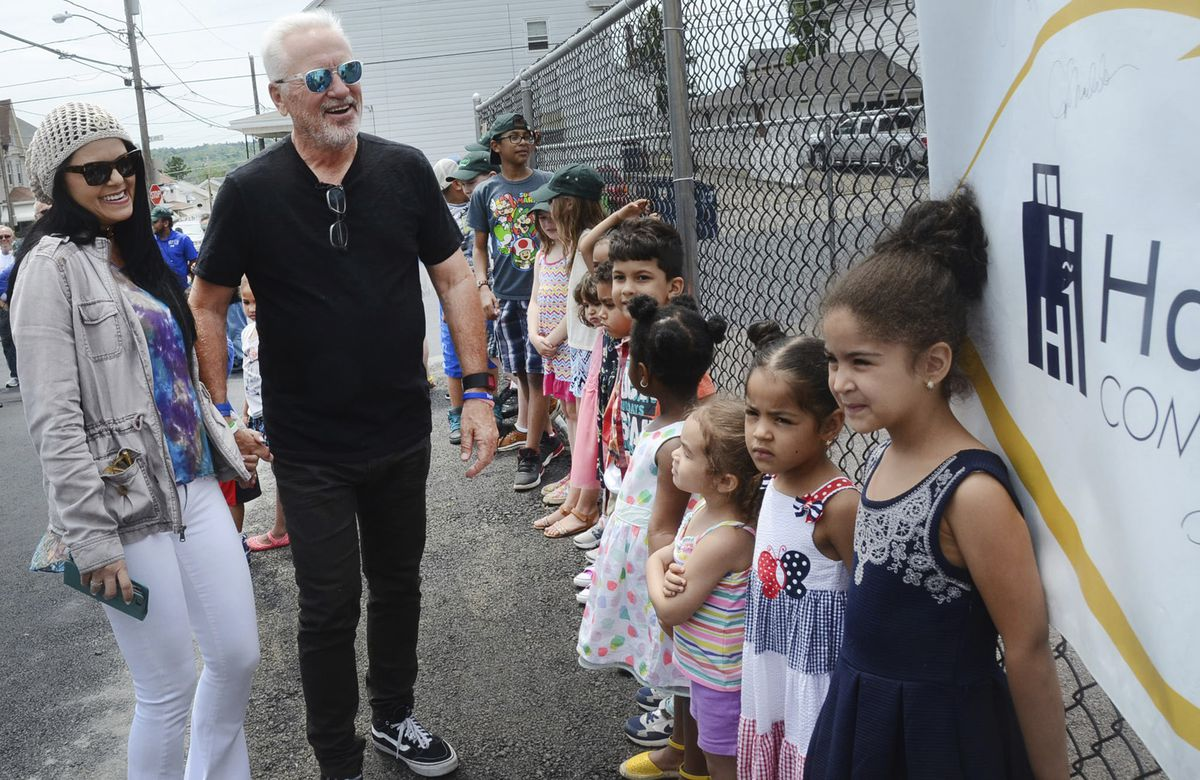 Chicago Cubs Manager Joe Maddon and his wife Jaye are all smiles as they see the new playground at the Hazleton One Community Center and the day care children waiting for it to open in Hazleton, Pa. | Ellen F. O'Connell/Associated Press