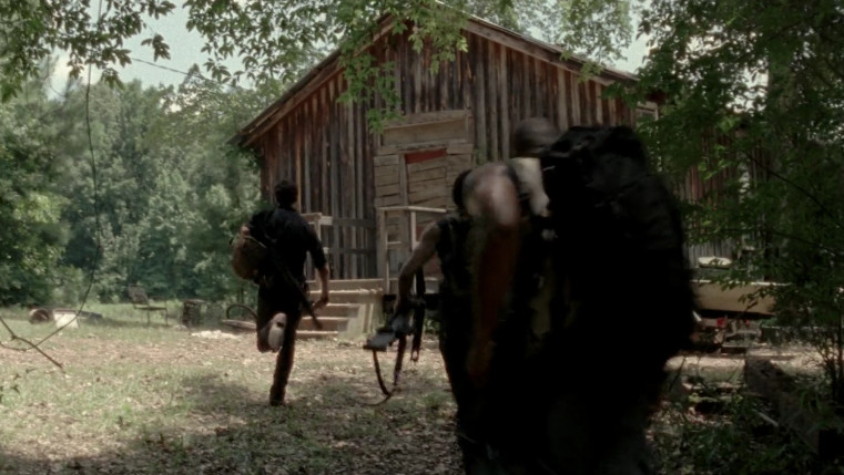People run towards a wooden cabin in the woods.