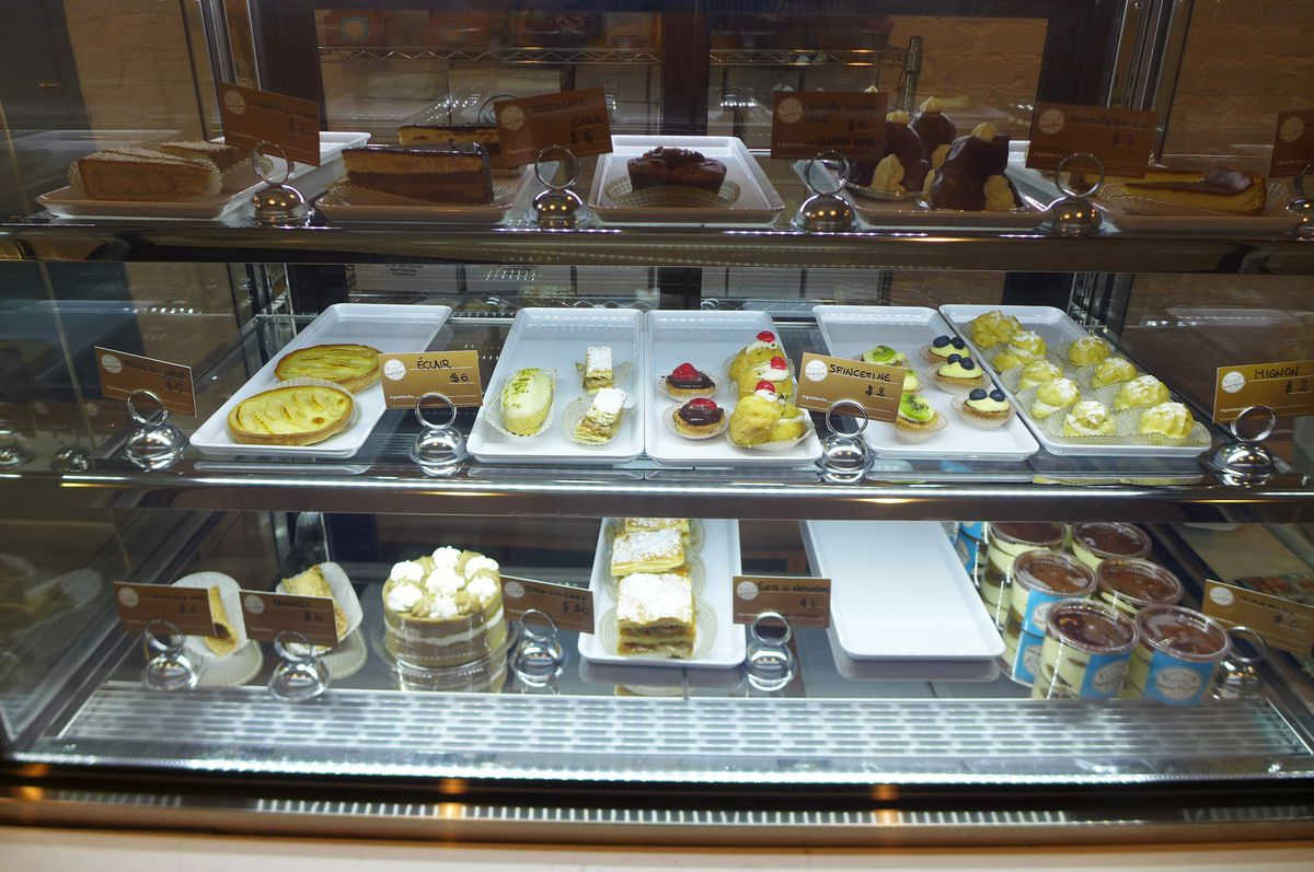 A pastry case filled with dramatically lit pastries.