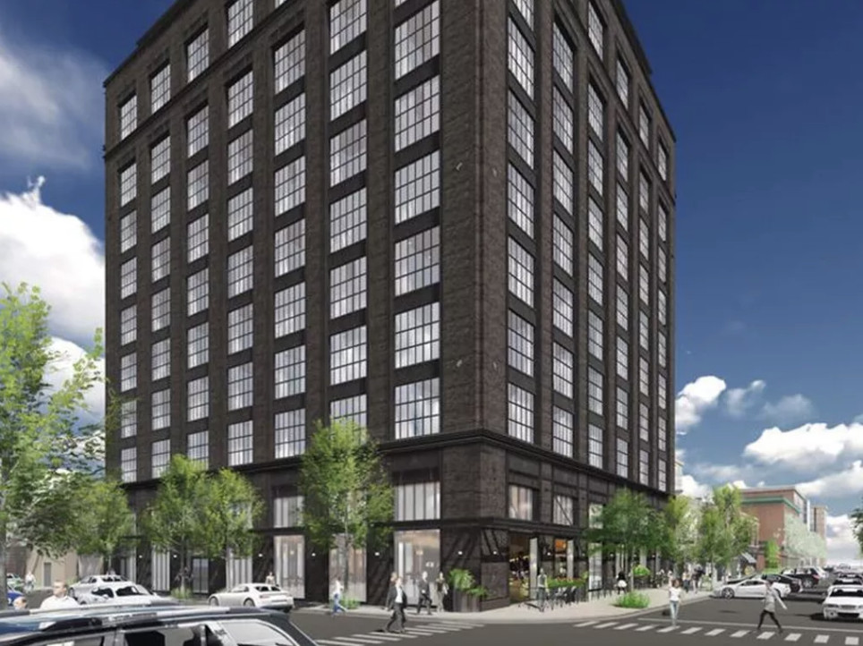 A dark brick hotel stands on a street corner it has a grid of oversized warehouse style windows, pronounced vertical piers, and a extra-height ground floor.