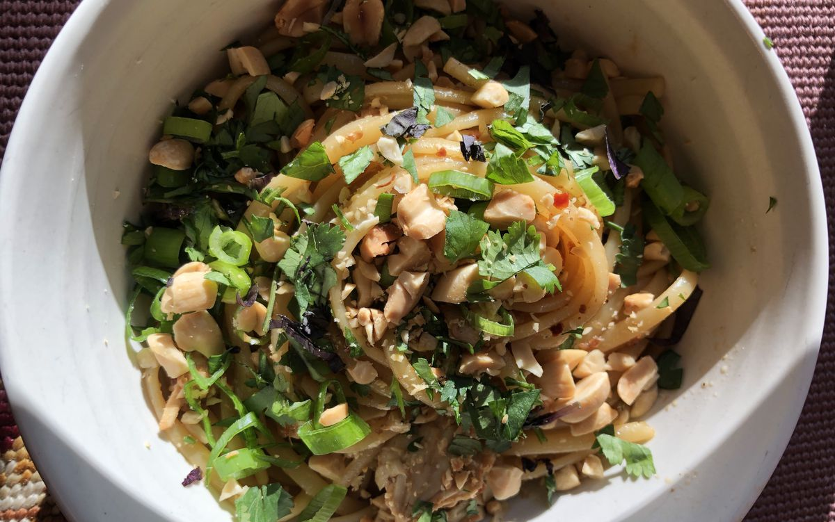 Noodles in a bowl with peanuts and herbs