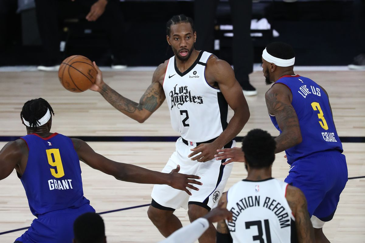 LA Clippers forward Kawhi Leonard passes the ball against Denver Nuggets forward Jerami Grant and forward Torrey Craig during the second half of game five in the second round of the 2020 NBA Playoffs at ESPN Wide World of Sports Complex.