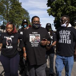 Jacob Blake's father, also Jacob Blake, walks with family members and supporters during a rally in Civic Center Park in downtown Kenosha, six days after his son was shot in the back by a police officer in the Wisconsin city, Saturday, Aug. 29, 2020.