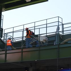 10:35 a.m. Workers in the left-field bleachers -