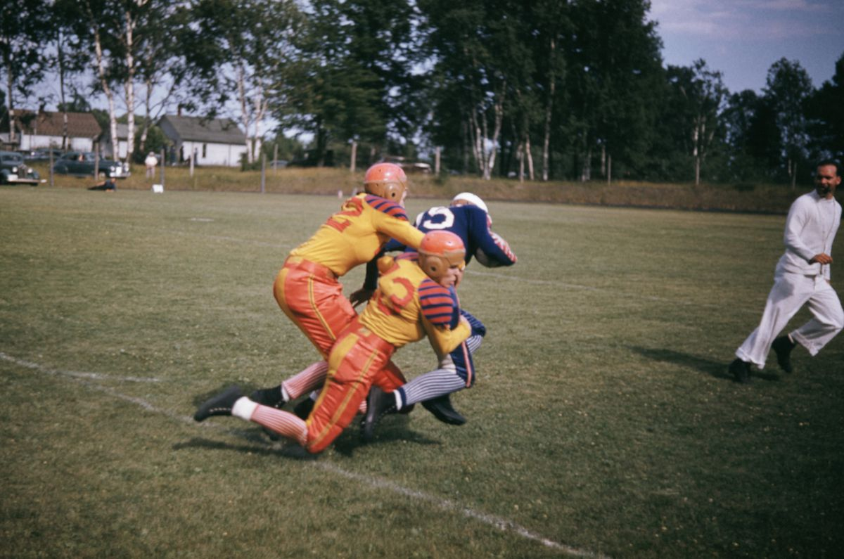 A pair of defenders tackle the ballcarrier during a football game in the 1940s.