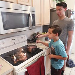 Lincoln, left, and Taylor Wakefield try to blow out a stove fire as they cook breakfast at their home in Kissimmee, Fla., on Monday Dec 21, 2020.