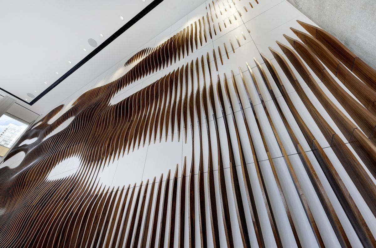 A white concrete wall with an abstract sculpture made of curved strips of wood.