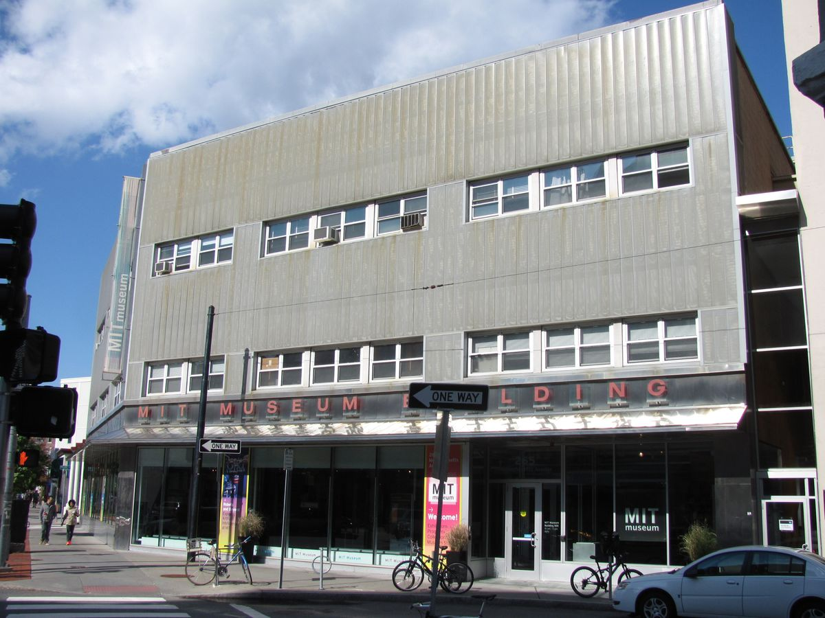 A boxy, three-story building on a busy street.