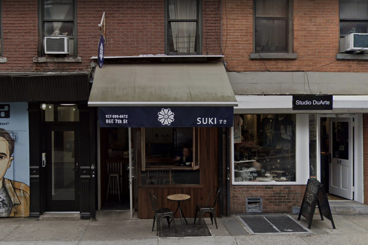 The exterior of the restaurant Suki, pictured with a dark blue awning and one table and two chairs set up outside