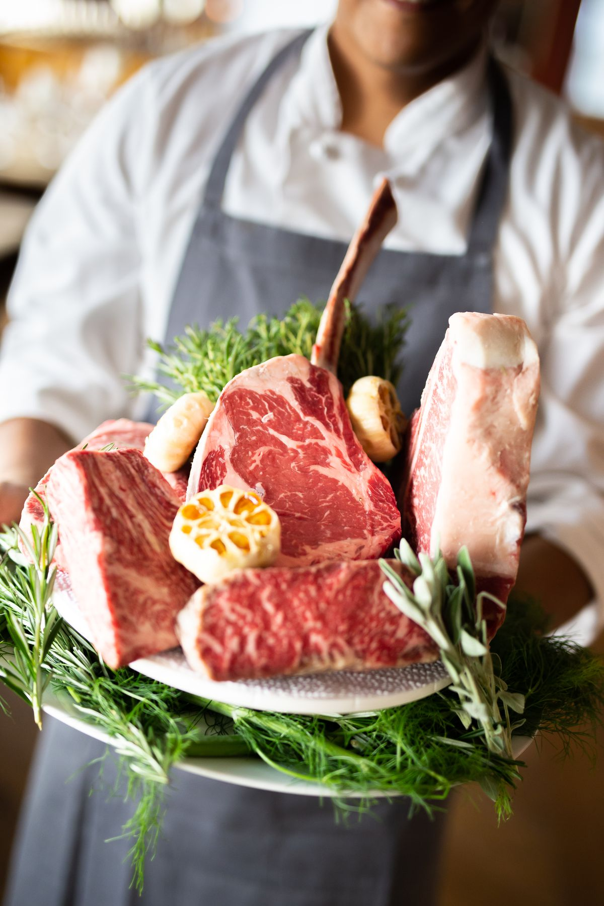 A staffer shows a variety of raw steaks on a plate decorated with rosemary