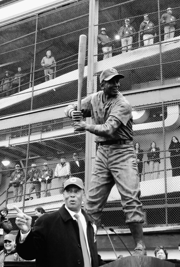Chicago Cubs Hall of Fame baseball player Ernie Banks talks about his career at the foot of his newly unveiled statue outside Wrigley Field during ceremonies in Chicago, Monday, March 31, 2008. (AP Photo/Charles Rex Arbogast)