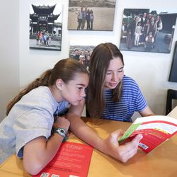 Katrina Hilton, left, listens as her sister, Maria, reads from a book written in Chinese in their home in Orem on Thursday, June 25, 2020. The girls and three of their siblings attend dual language immersion schools.