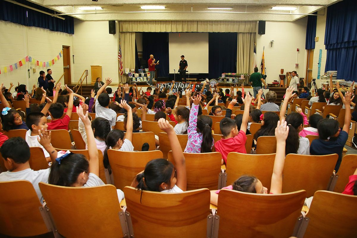 Dallas elementary school students raise their hands at an event in 2016.
