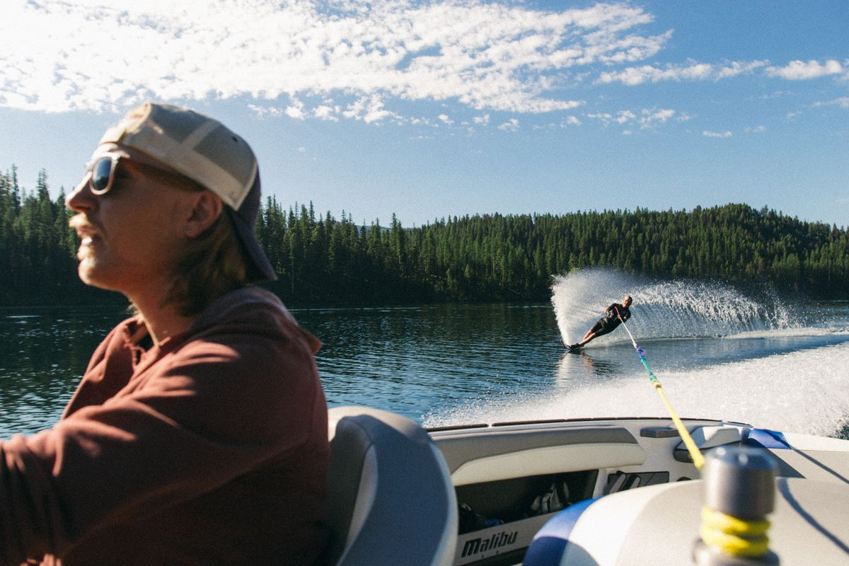 Joel Jewett drives a boat as his son Connor waterskis behind him.