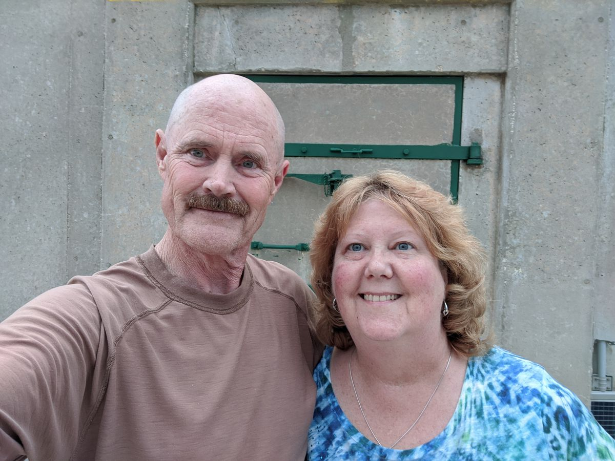 A photo of Tom and Mary smiling, taking a selfie photo outside their bunker.