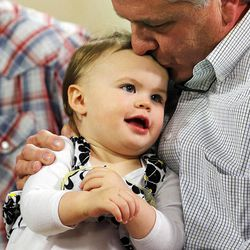 Chad Groesbeck holds his granddaughter, Lily Groesbeck, during an interview in Salt Lake City, Monday, March 16, 2015. The 18-month-old survived 14 hours trapped in a car upside down in the Spanish Fork River.
