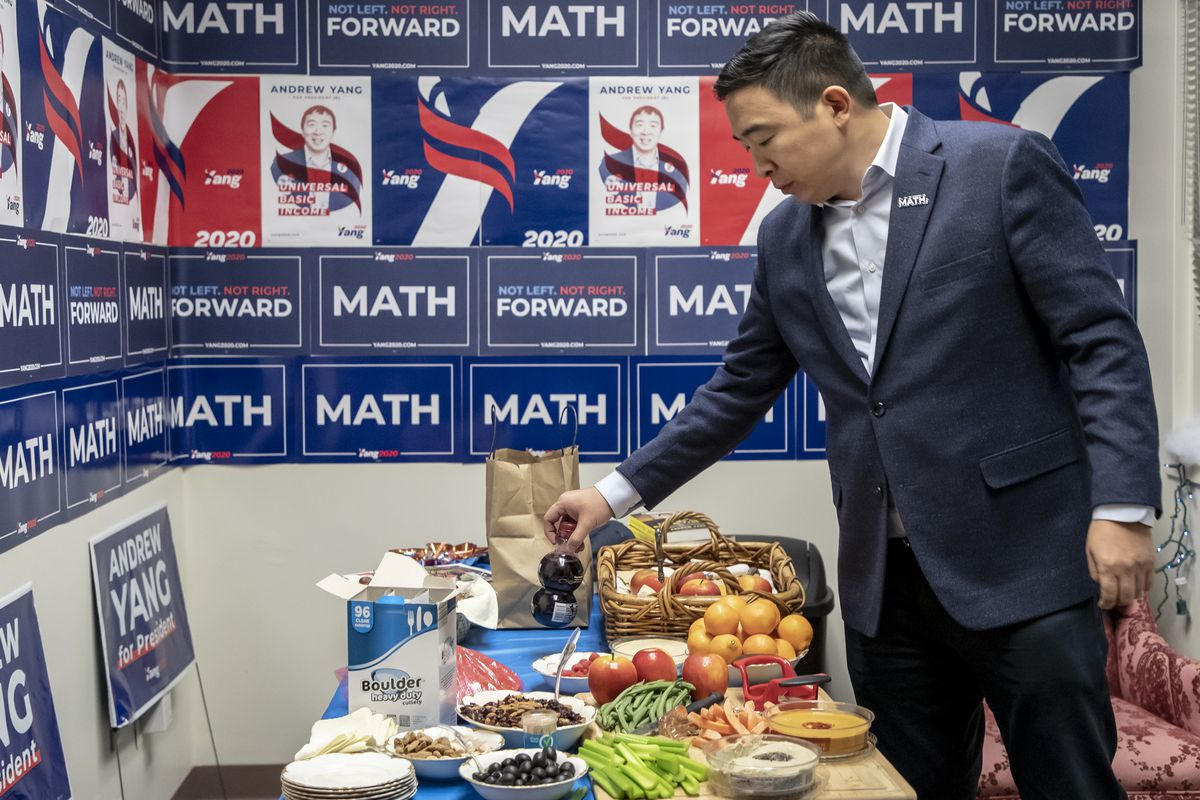 Yang hovers over a table with healthy snacks, his campaign posters in the background.