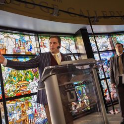 """Artists Tom Holdman, left, and Cameron Oscarson say a few words after the unveiling of the """"Roots of Knowledge"""" stained glass window display at the Utah Valley University library on Friday, Nov. 18, 2016, in Orem."""