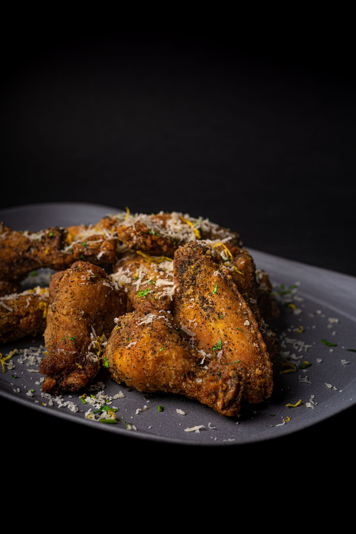 plate of chicken wings with graded cheese